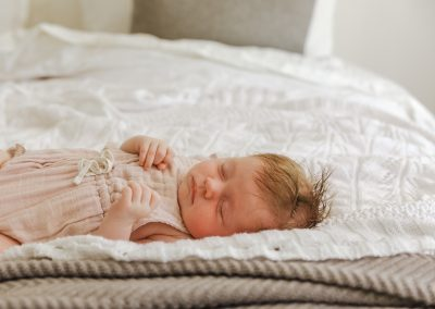 Baby girl sleeping, lying across the bed. She's wearing a pale pink outfit, lying on a white blanket with a grey throw and grey cushions